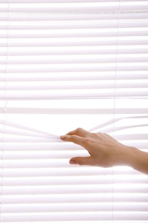 hands apart on the window blinds.. photo
