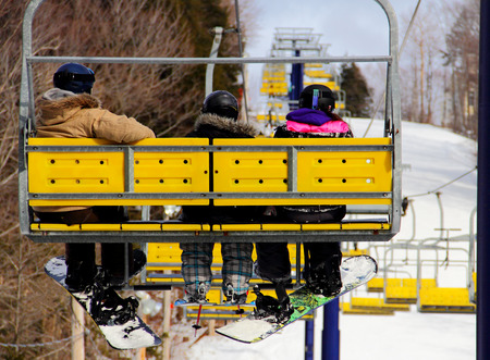 A family of two snowboarders and a skier riding up in a chairlift during winter at a sky resort in Bromont, quebec, Canada photo