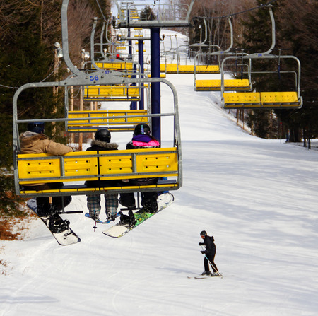 Chairlift system featuring a group of skier and snowboarder riding up the hill while a skier is going down the snowy slope underneath photo