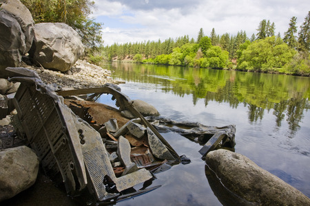 dumped: Horizontal photo of eroding television dumped in a river