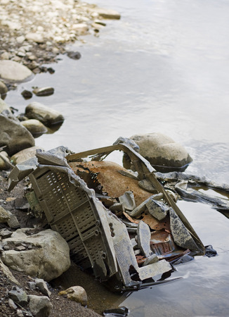 dumped: Vertical photo of eroding television dumped in a river