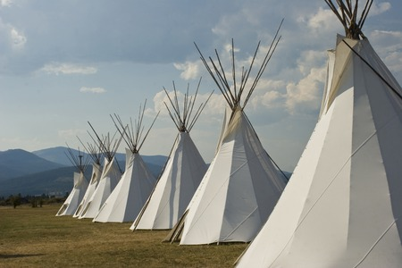 Seven Native American Teepees on grass in front of wooded hills with blue sky Stock Photo