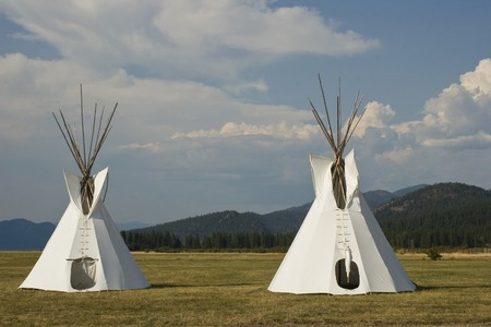 Two Native American Teepees on grass in front of wooded hills