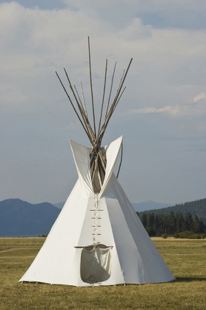 Native American Teepee on grass in front of wooded hills Stock Photo