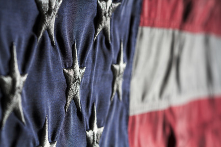 Horizontal close up Shot of American flag focused on the white stars in blue field with blurred red and white stripes