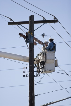 Vertical Photo of Linemen Utility Workers working on phone lines from bucket truck with blue sky