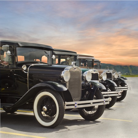 Photo of Four vintage Ford Model A automobiles parked in lot with sunset in background