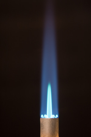 butane: Vertical Photo of copper Torch tip with Blue Flame and Copy Space on black background