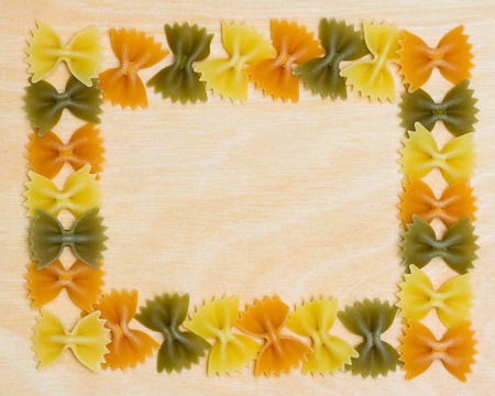 semolina pasta: Horizontal photo of Tri Color Bow Tie Pasta arranged as border on wooden background.