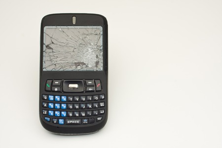 Horizontal Photo of Cell phone with shattered screen on white background with copy space photo
