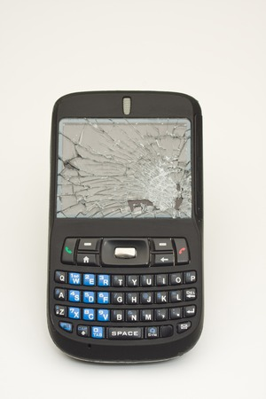 old cell phone: Vertical Photo of Cell phone with shattered screen on white background with copy space Stock Photo