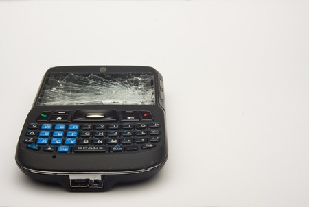 white backing: Horizontal Photo of Cell phone with shattered screen on white background with copy space Stock Photo