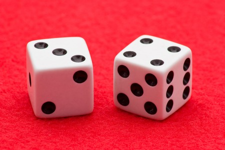 Horizontal Photo of Two white dice with black dots displaying craps seven on two sides on red felt background