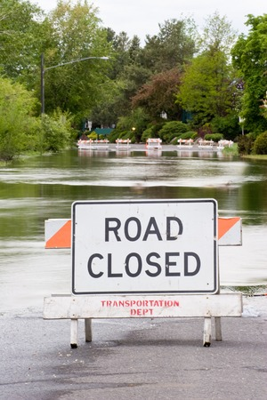 overrun: Vertical photo of a Road Closed sign standing in front of flood waters from nearby Spokane river, Washington State Stock Photo