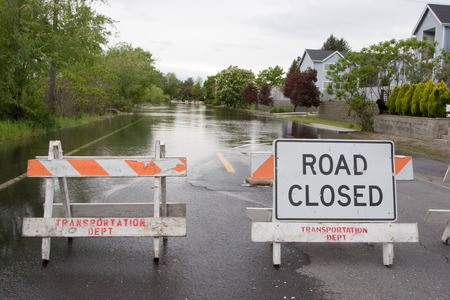 overrun: Horizontal Photo of A Road Closed sign standing in front of floodwaters from nearby Spokane river, Washington State Stock Photo