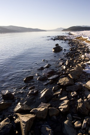 crescent lake: Vertical photo of Rocky Winter Shoreline on Lake Pend Oreille Idaho with mountains in background and traces of snow near Sandpoint and Hope