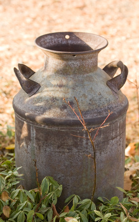 Horizontal Photo of an Antique Milk Can on farm with direct sunlight, foreground and background Stock Photo