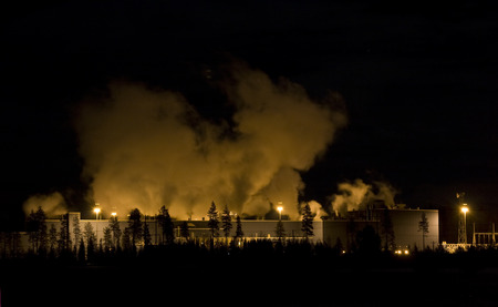 emit: Horizontal photo of a Factory or plant at night with steam or smoke clouds over it in the distance