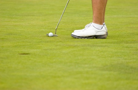 18th: Horizontal Photos of male legs with feet, shoes, putter, ball, hole on green grass