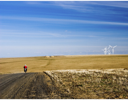 repurpose: Motorcycle riding towards Group of Wind Mills on windfarm on a cloudy day