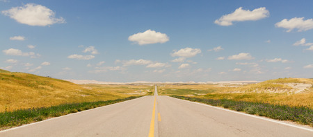 Horizontal Photo of an Ultra Wide North Dakota Highway with yellow lines, blue sky and clouds Stock Photo