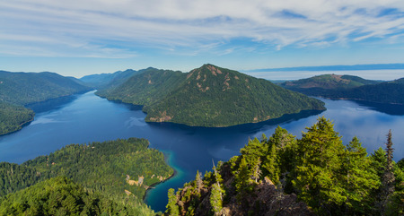 Horizontal photo of a View of Lake Crescent in Olympic National Park from Storm King with blue skies and clouds reflecting in the blue water. Mountains and hills in the background with evergreen trees in the foreground.
