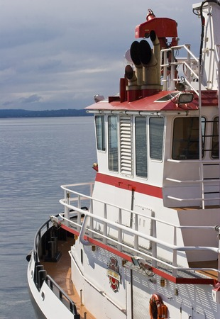 Vertical Photo of a red and white fireboat docked on blue water with clouded skies