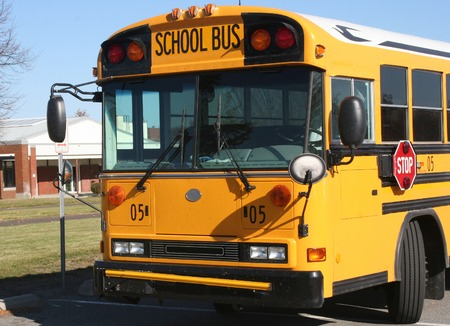 Horizontal photo of a yellow School bus parked in front of a building on a clear sunny day and waiting on clear day Stock Photo