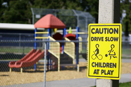 Horizontal Photo of a Caution Drive Slow Children Playground sign in front of a playground