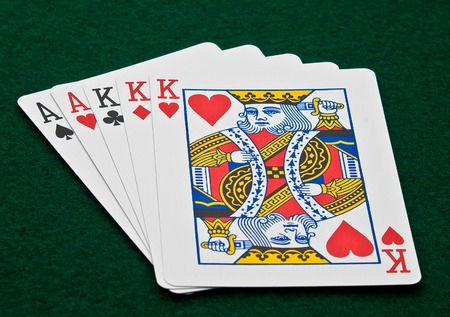 Horizontal photo of Poker hand full house aces and kings with king of hearts suicide king on green felt Stock Photo