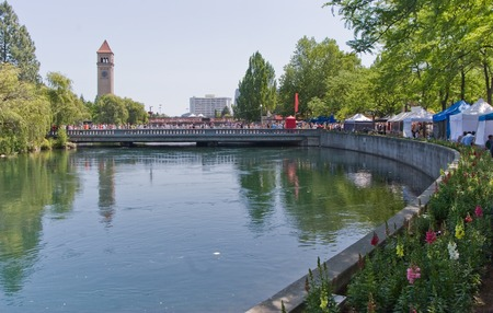 Spokane River in Riverfront Park with Clock Tower flowers, people, bridge and vendors 스톡 콘텐츠