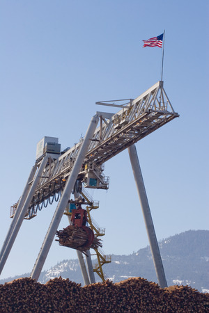 Vertical Photo of a Logging Crane with American Flag, Blue Sky and Mountains 스톡 콘텐츠
