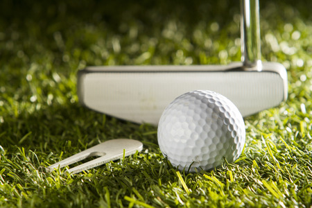 Close up horizontal shot of golf ball, putter and divot tool on green grass