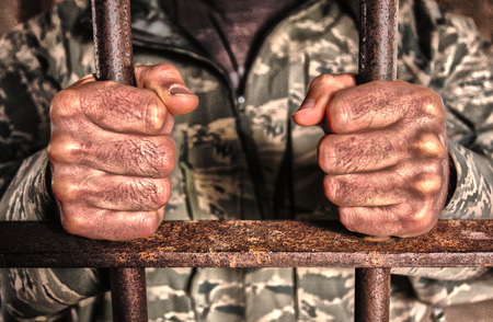 jail: Gritty horizontal photo of man in camouflage clothes holding rusty iron jail cell bars