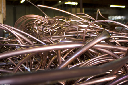 Bin of recycled copper tubing in lit warehouse