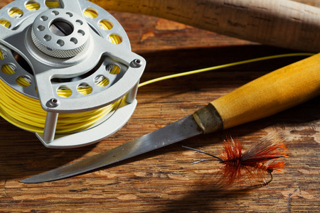 Horizontal photo of Fly Fishing gear on wood table top