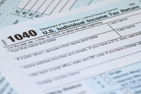 Macro horizontal photo of a 2013 1040 IRS Tax Form laying on second page of form