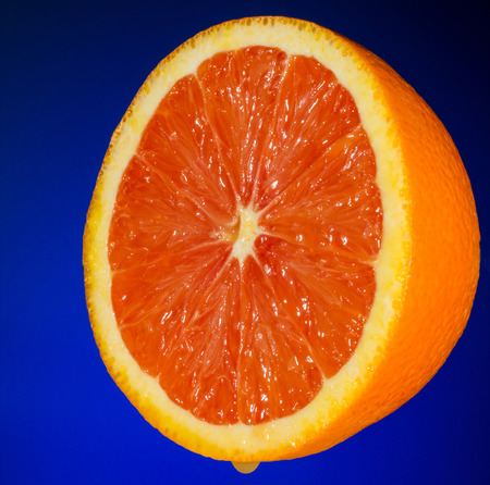 Photo of Isolated Juicy Orange half on Blue Background dripping juice