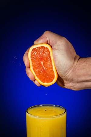 Vertical Photo of fingers squeezing fresh orange juice from a sliced orange half into a clear glass with a blue background and copy space Stock Photo