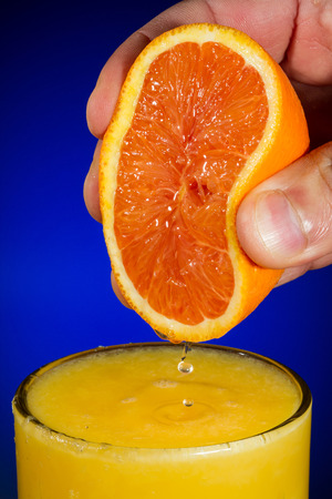 Vertical Photo of fingers squeezing fresh orange juice from a sliced orange half into a clear glass with a blue background