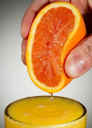 Vertical Photo of fingers squeezing fresh orange juice from a sliced orange half into a clear glass with a white background