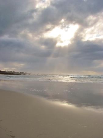 Rays of Sun through the clouds on a beach