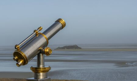 spyglass in first line of sea, of silver and gold chlorine next to a wall