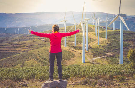 woman in red mountain clothes, with open arms in the form of a cross, enjoys her freedom and happiness and contemplates a wind farm and the mountains