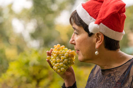 happy woman enjoys a bunch of white grapes at Christmas and wears a Santa Claus hat