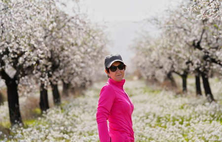 Woman in green cap and fuscia T-shirt poses in a field of almond blossoms and white flowers.