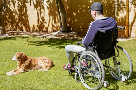 Disabled young man sitting in a wheelchair and taking fresh air in his garden and enjoying life.