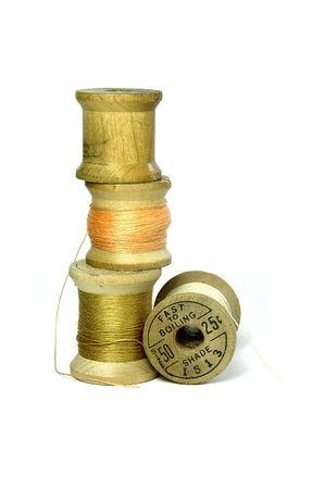 slacks: 1940s wood spools and thread on white background
