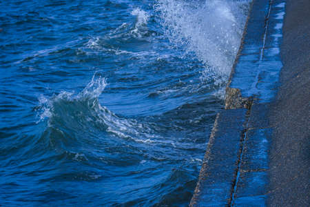breakwaters: Deep blue waves and spray when the waves hit the cement breakwater.  Stock Photo