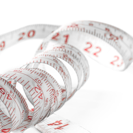 Measuring tape, mostly used for tailoring, lying all curled up on a white backdrop. photo